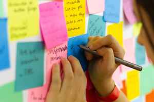 person writing on pink sticky notes