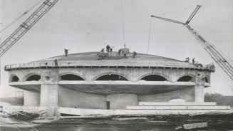 Dome under construction, construction cranes lifting concrete onto roof. Photo Credit: October 1960 AP Wire photo. Collection of Eric M. O'Malley.)