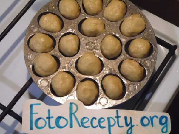 Разложите шарики из теста по отверстиям в сковороде.