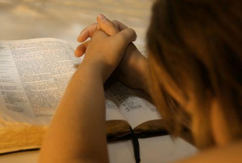 mujer orando sobre biblia