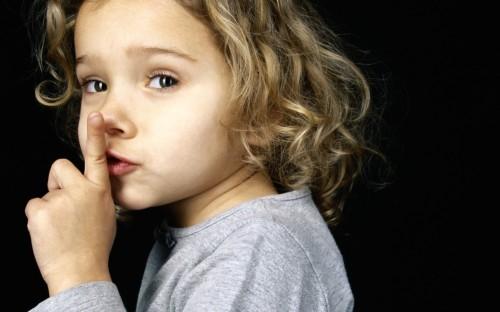 niña haciendo gesto de silencio fondo