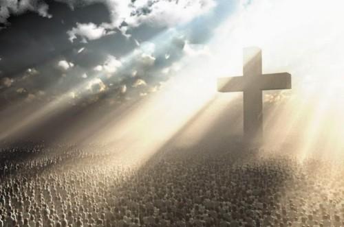 cruz iluminada con gente abajo aviso