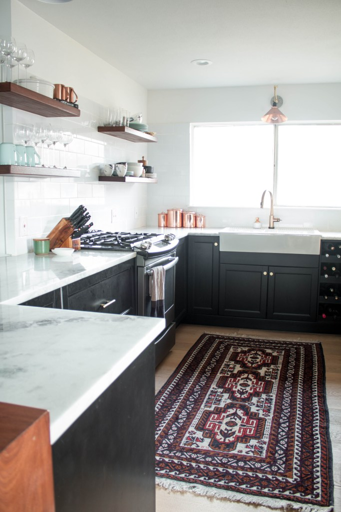bohemian modern kitchen with black cabinetry, kitchen rug, open shelving, marble countertops, and copper kitchen accents // full kitchen renovation at fortheindoorsy.com