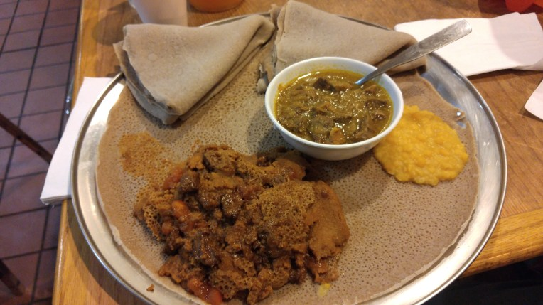 Tibs firfir and alicha wot with a side of kik alicha on a platter of injera at Zenebech in D.C., November 2015.