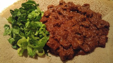 A plate with siga wot (cubed beef in spicy sauce) and very green lettuce salad.