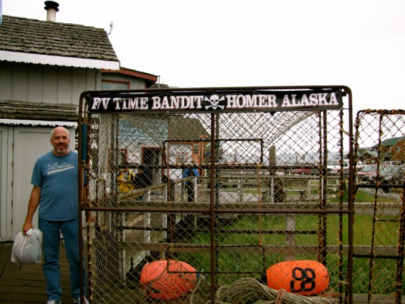 My dad by a crab pot in front of the Time Bandit Store