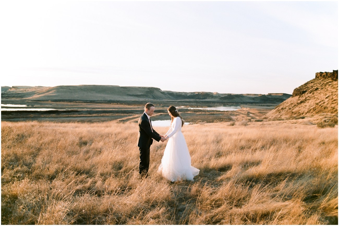 Large panorama of a bride and groom standing in a meadow at sunset by Forthright Photo