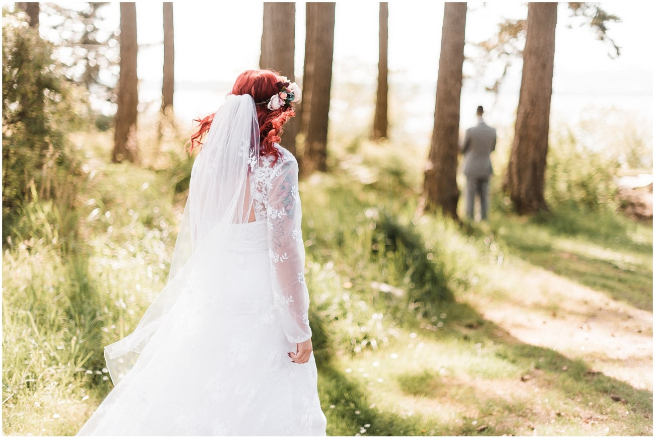 Photo of a bride walking through the woods to her first look