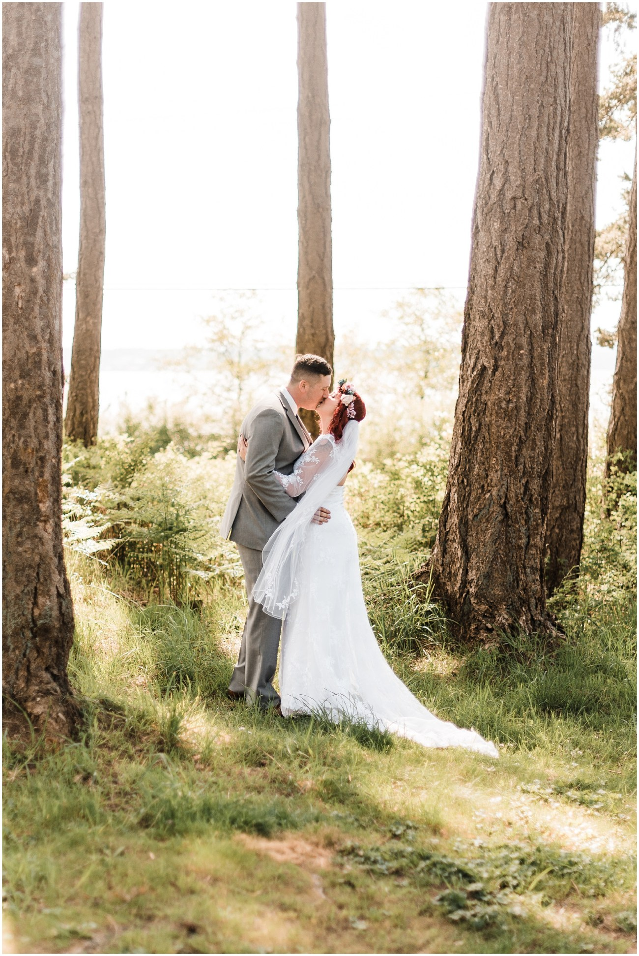 Photo of a bride and groom kissing in a forest during their first look