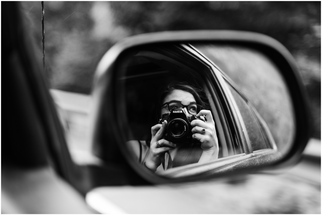 Black and White photo of Laura taking a picture in the side mirror of the car