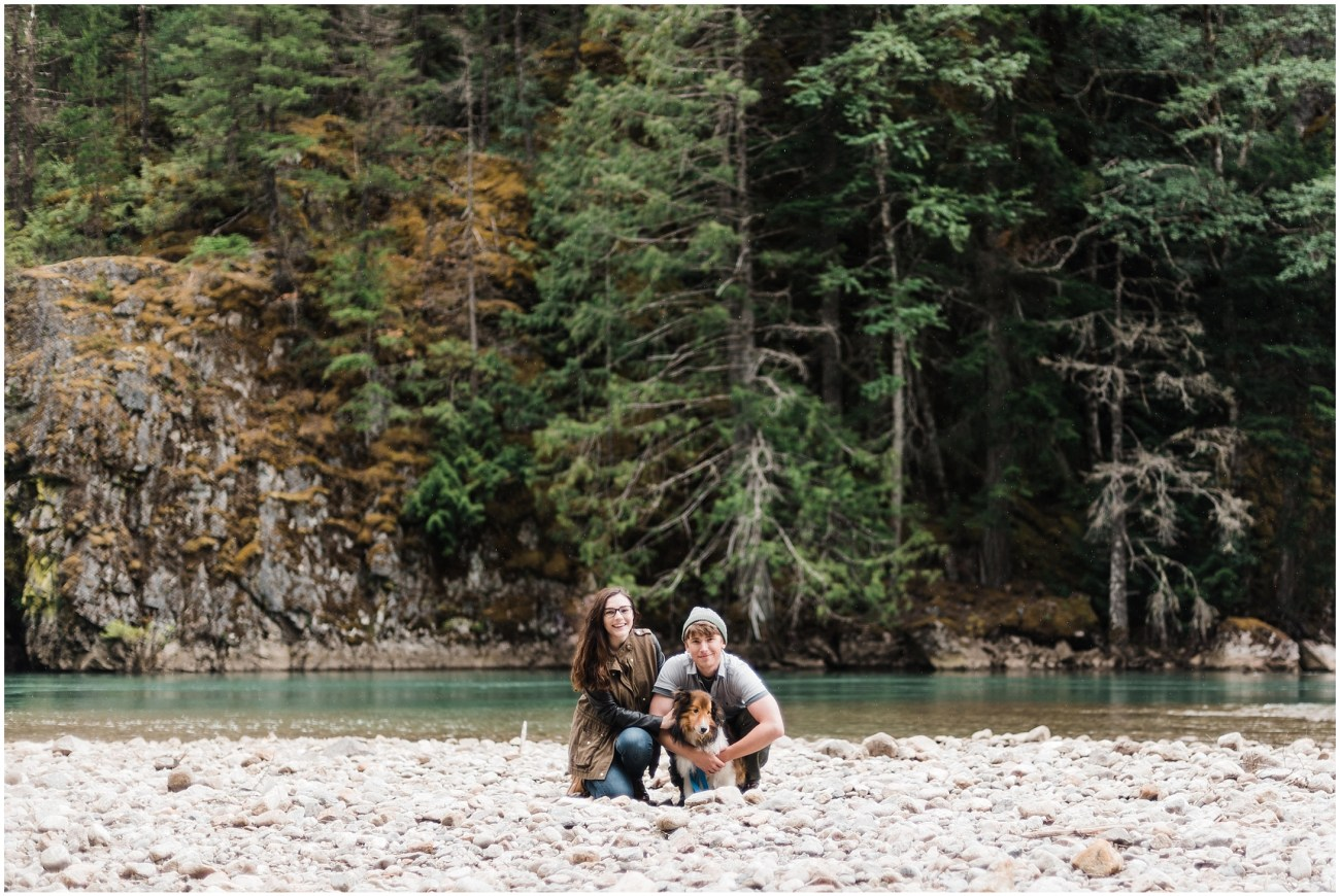 A photo of Laura, Devon, and their dog Simon in front of a river in North Cascades National Park