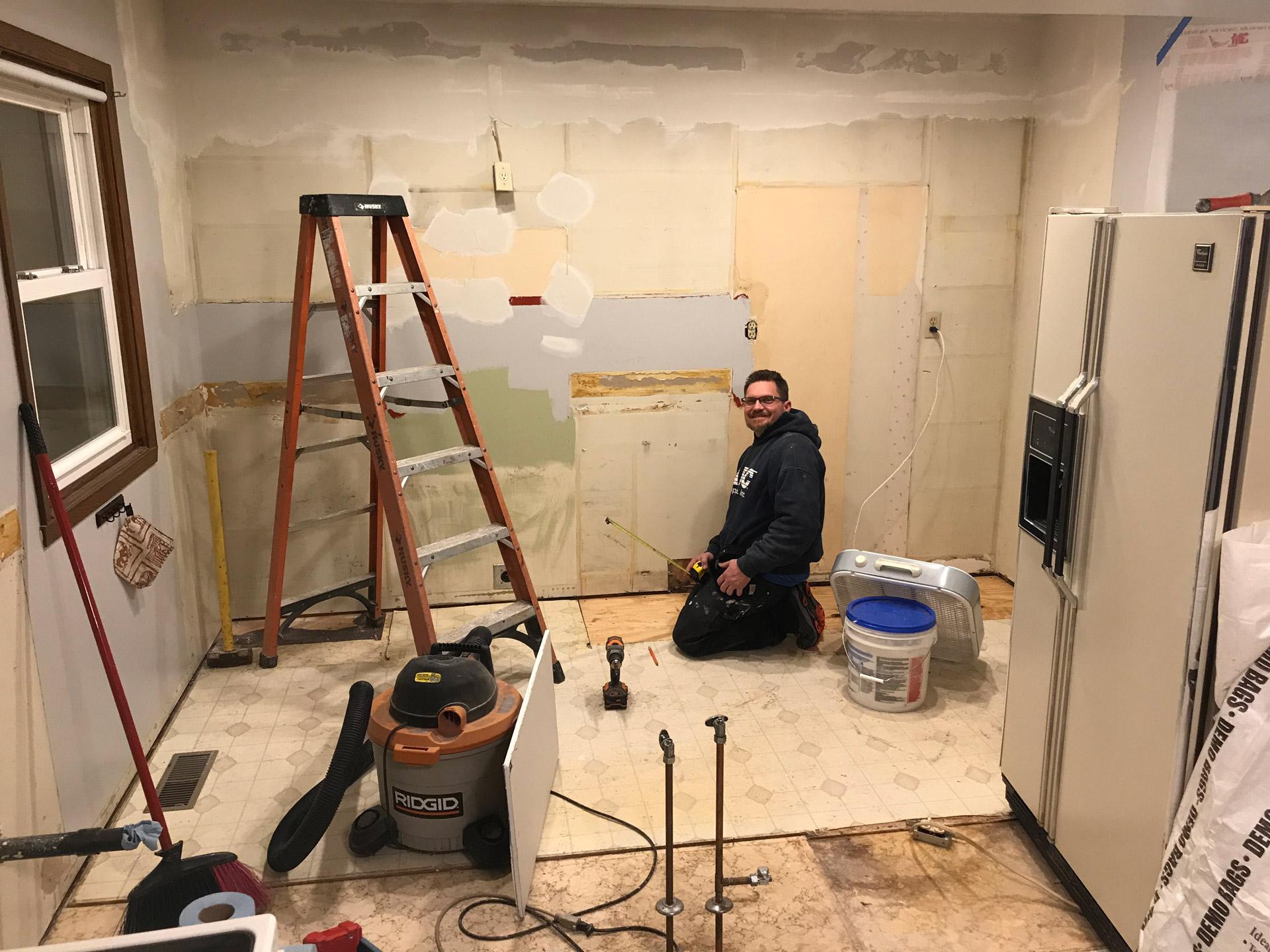 Brandon Perry kneeling in demo'd kitchen