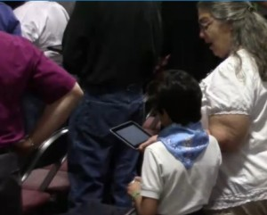 A young attendee at General Convention joins in worship.