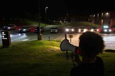 """Renee White, left, holds up a fist in front of the barricade of eight police cars as Elijah Lyons, Marvin Scott III's 9-year-old nephew, leads a chant repeating Marvin's name at the Collin County Jail on April 3, 2021. The police moved them out of an area where they were decorating a fence, spelling out """"Justice 4 Marvin III""""."""