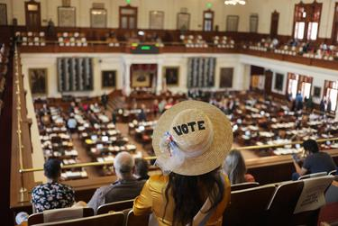 A visitor of the House gallery listens to legislators speak during a debate on an abortion bill being considered on the House floor on May 5, 2021.