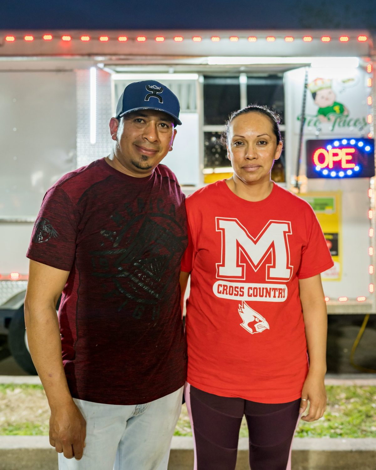 A man and a woman standing next to each other in front of a taco truck.