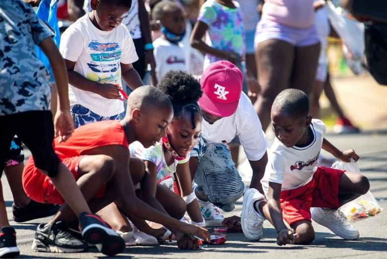 Children scramble for candy during the annual Juneteenth parade in East Austin on June 19, 2021. Juneteenth commemorates Union Army General Gordon Granger's proclamation issued on June 19, 1865 in Galveston, which ordered the freedom of more than 250,000 enslaved Black people in Texas who were denied freedom for more than two years after President Abraham Lincoln signed the Emancipation Proclamation.