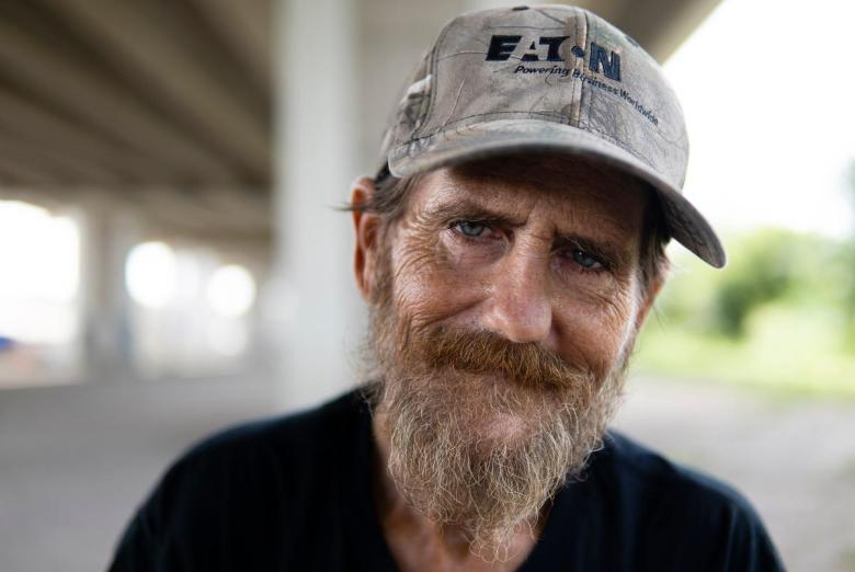 Derek Lorentzson, 48, sits in front of his tent underneath Ben White Blvd. on July 27, 2021. He has been unhoused for ten years.