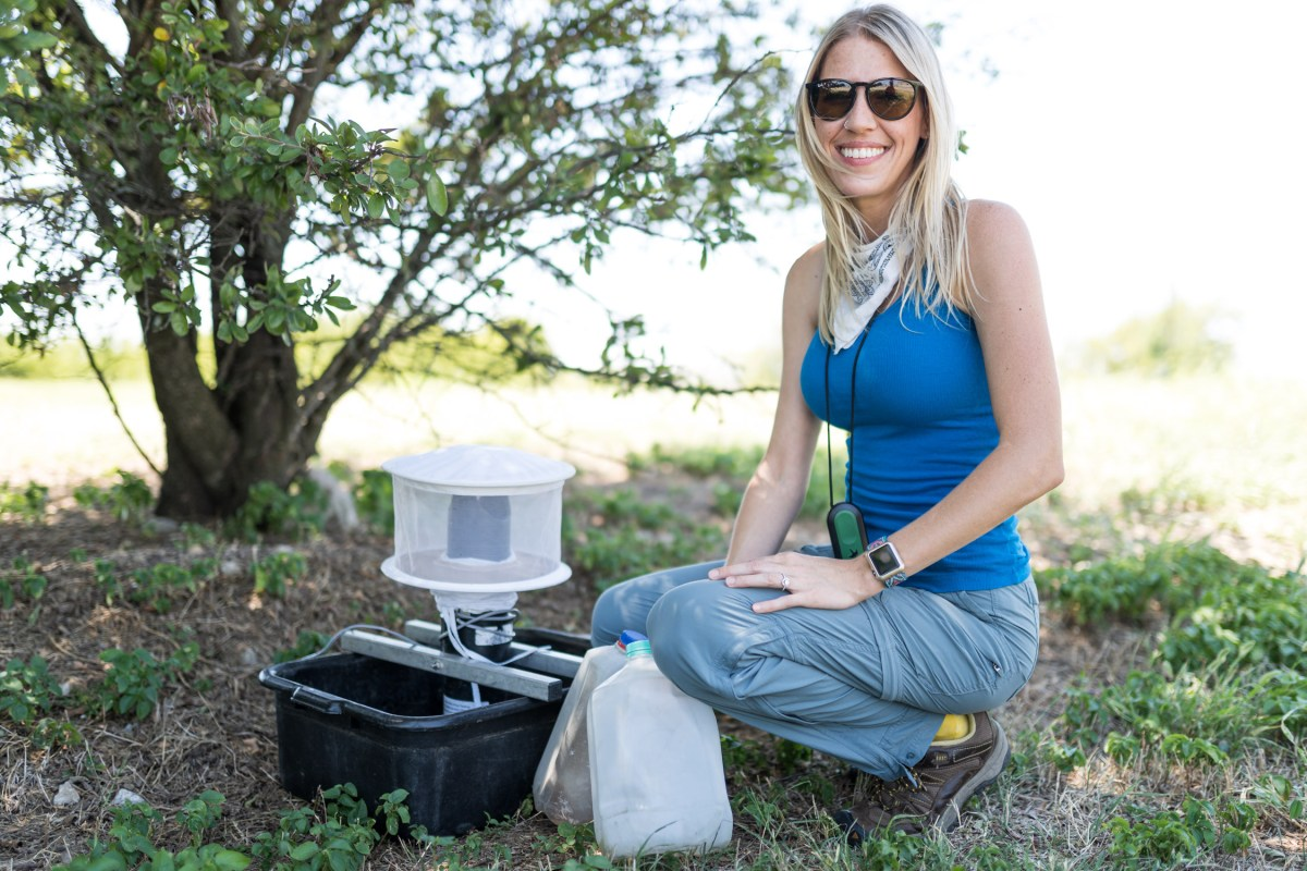 Bethany Hambrick smiles while setting up a mosquito trap.