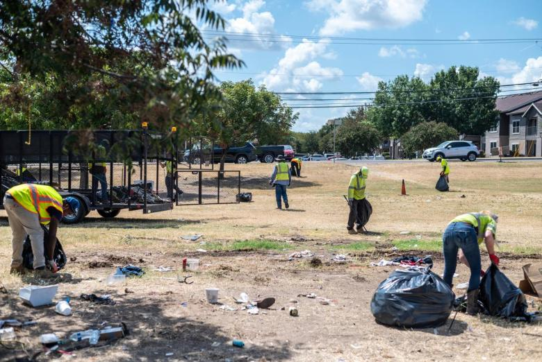 City workers clear out a former homeless encampment off Riverside Drive on Sept. 28, 2021 in Austin. Many of the people who had been living in the camp said they weren't given enough notice and were not offered any place to stay. Sergio Flores for The Texas Tribune