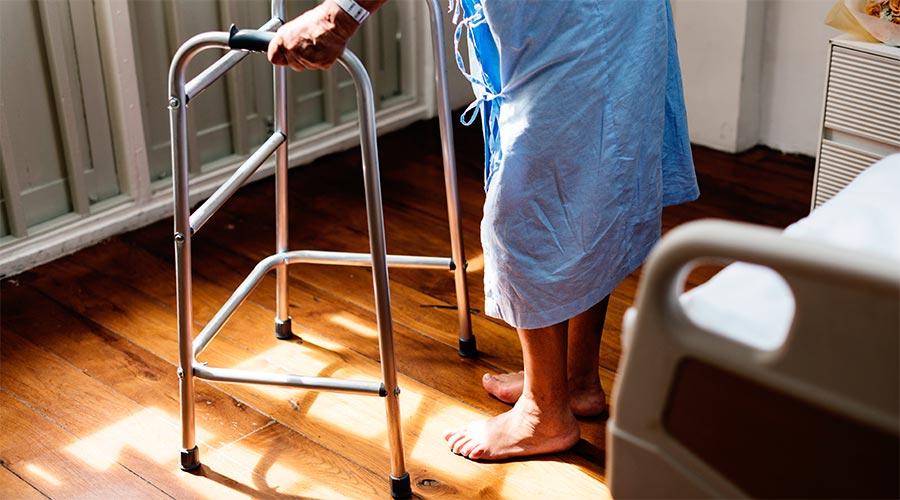 Una persona de peu amb l'ajuda d'un caminador