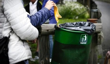 Escolars dipositant residus en una paperera