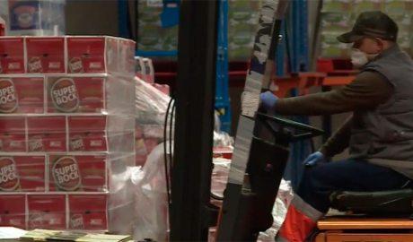 UN treballador protegit amb mascareta i guants treballa en un magatzem d'alimentació