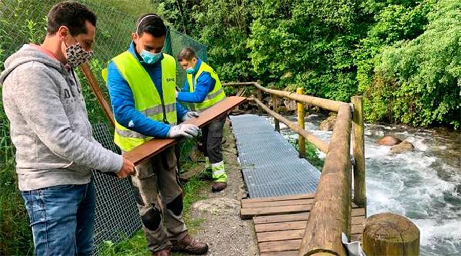 Operaris fent els treballs de manteniment a la passarel·la del camí Ral de la Massana