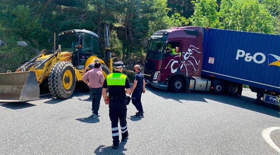 Operaris i agents de circulació ajuden un camió que ha quedat travessat a la carretera dels Cortals