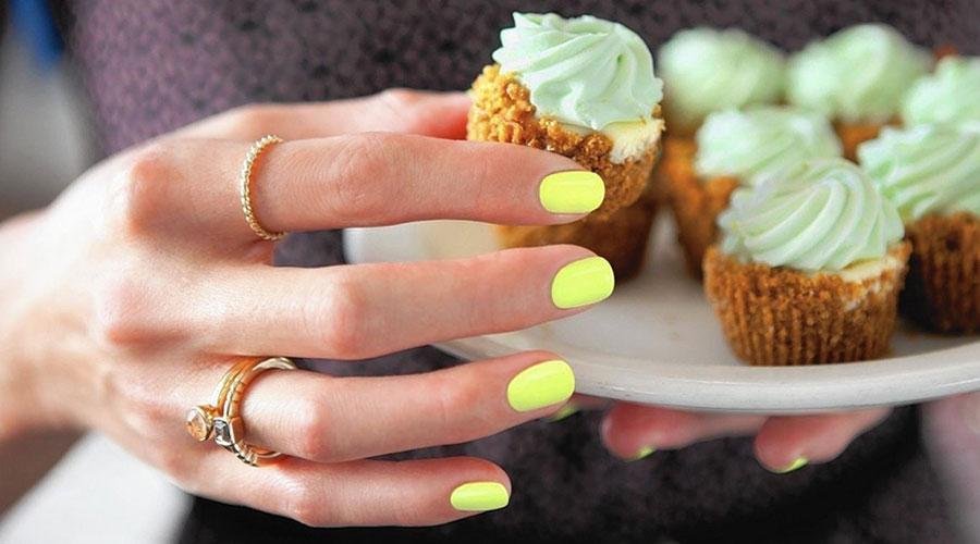 Una ma amb les ungles pintades de groc agafant pastissets