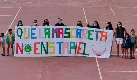 """Un grup de joves i infants sostenen la pancarta on es llegeix el lema """"Que la mascareta no ens tapi el somriure"""""""