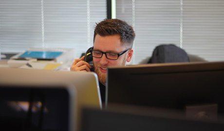 Un home parla per telèfon estant en una oficina