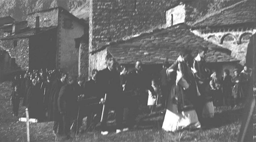 Comitiva d'un enterrament al cementiri vell d'Andorra la Vella. Es veu part de l'absis de l'església de Sant Esteve. Any 1900-1930 CRA_Arxiu Nacional d'Andorra