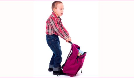 Nen arrossegant una motxilla molt pesada