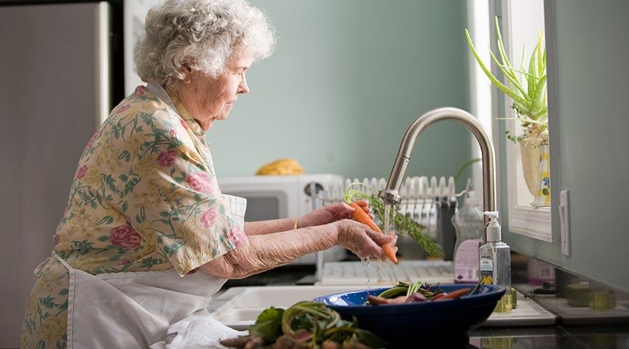 Una padrina renta verdures sota un raig d'aigua a la pica d'una cuina