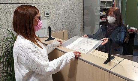 Una graduada de la promoció 2020 recull a la recepció de la Universitat el seu títol de bàtxelor en Administració d'empreses. Foto: UdA.