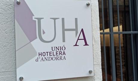 Cartell amb el logotip de la Unió Hotelera d'Andorra a la porta del seu local