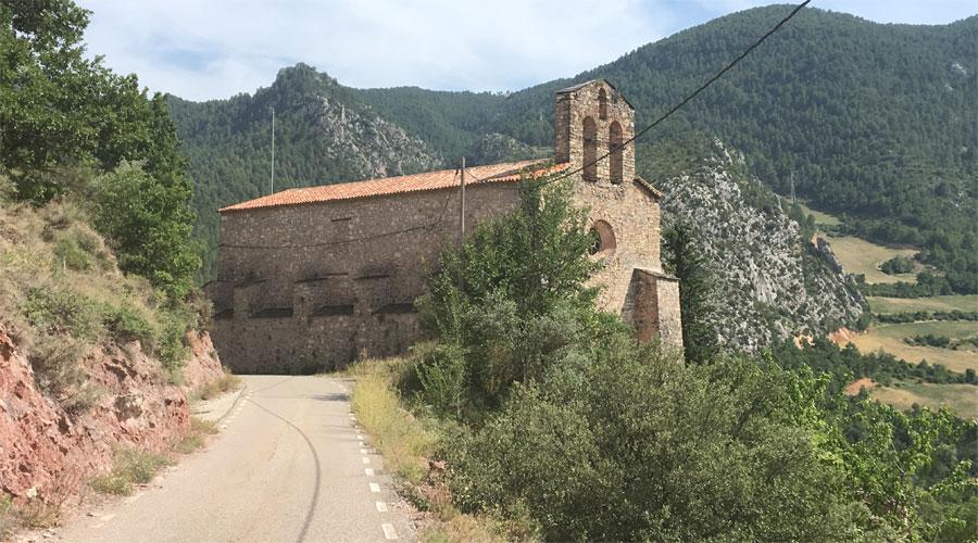 Una carretera passa pel costat d'una església a la Vall de Tost