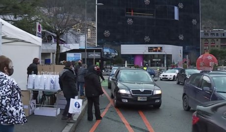 Cotxes passant per la plaça dels Arínsols a recollir la bossa amb les racions d'escudella
