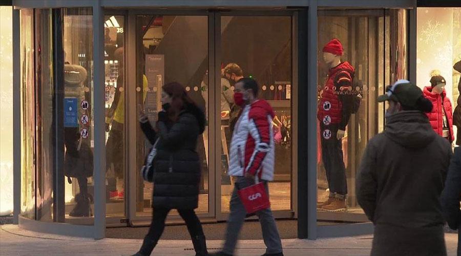 Uns turistes passant davant d'un establiment comercial