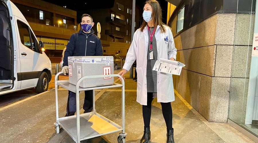 El transportista entrega a una responsable del SAAS les primeres vacunes de Covid-19 que arriben al país