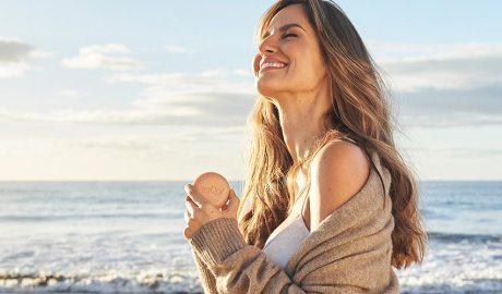 Una noia amb una pastilla de sabó davant del mar