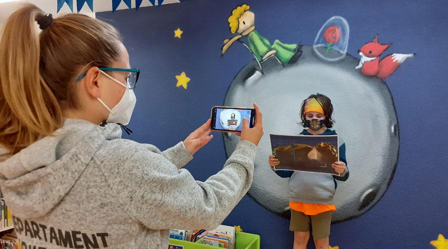 Una monitora grava un infant llegint un fragment del Petit Príncep