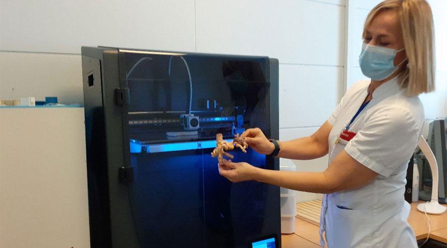 Una professional del SAAS mostra dues impressions davant la impressora 3D