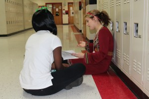 Belmont student Katlin Stodard, right, tutors a high school student on the hallway floor.