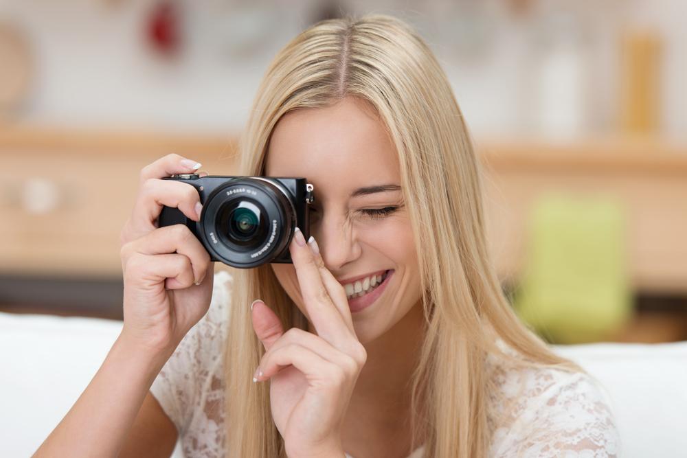 mujer sosteniendo una camara digital