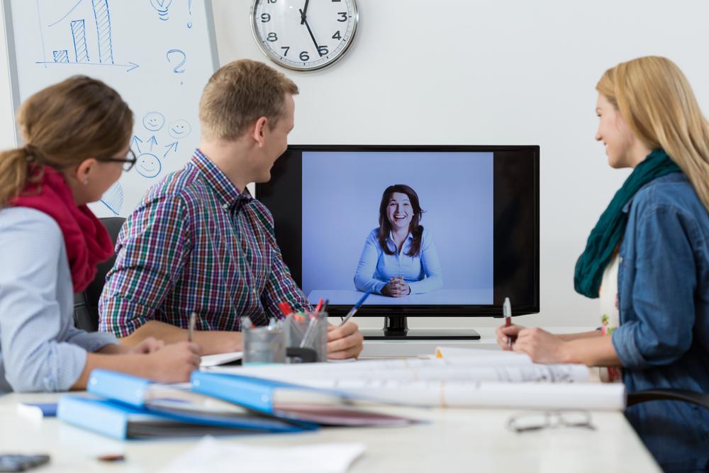 grupo de personas sentadas frente un monitor con video conferencia