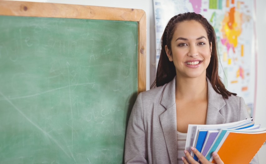 docente con libros en mano y una pizarra de fondo