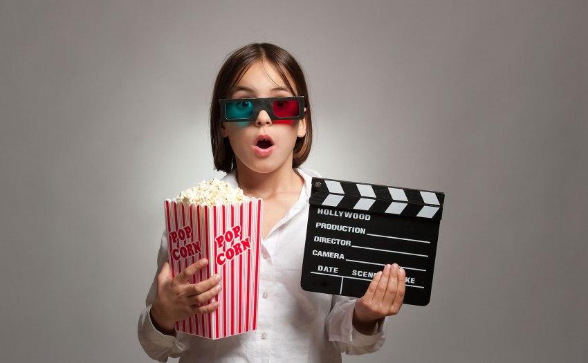 Niña con gafas 3d, popcorn y claqueta de cine