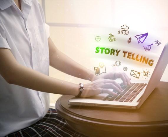 Niña en uniforme escolar sentada frente a una computadora escribiendo historias digitales